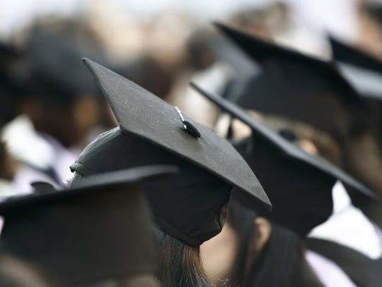 backs of heads of some graduates, wearing caps and gowns