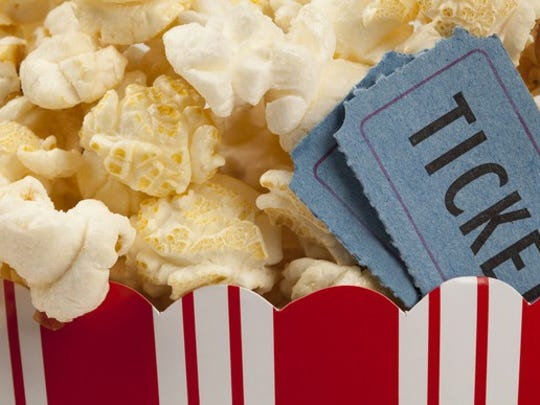 close up of two tickets stubs in a box of popcorn.