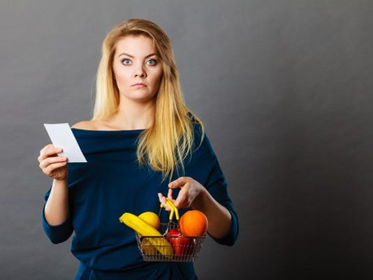 young-woman-holding-produce-and-receipt-upset-about-cost-price-sticker-shock-inflation_large.jpg