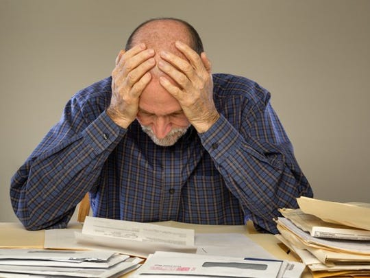 Man looking depressed over a stack of bills