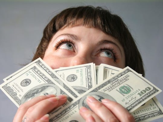 Young woman holding a stack of $100 bills