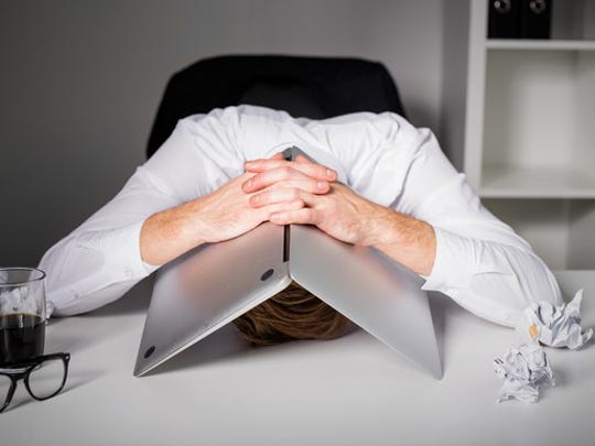 A man hides his head under a laptop