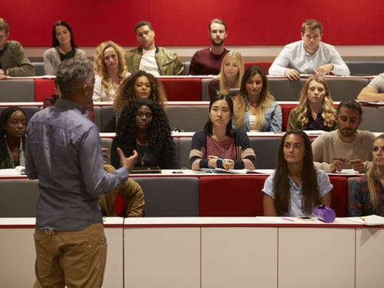 Students listen as a lecturer speaks to them.