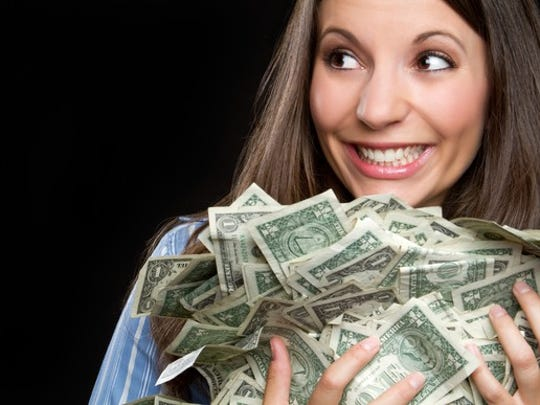 smiling young woman holding armful of one-dollar bills