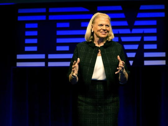 Ginni Rometty speaking at an IBM event, with the logo large behind her