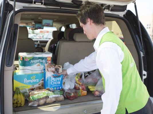 walmart-associate-loads-groceries-into-the-trunk-of-a-vehicle-for-grocery-pickup_large.jpg
