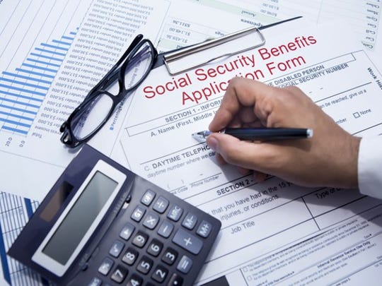 A person filling out a Social Security benefits application form, with glasses, a calculator, and other papers nearby.