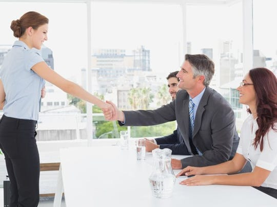 A woman shakes hands with a man at a job interview.
