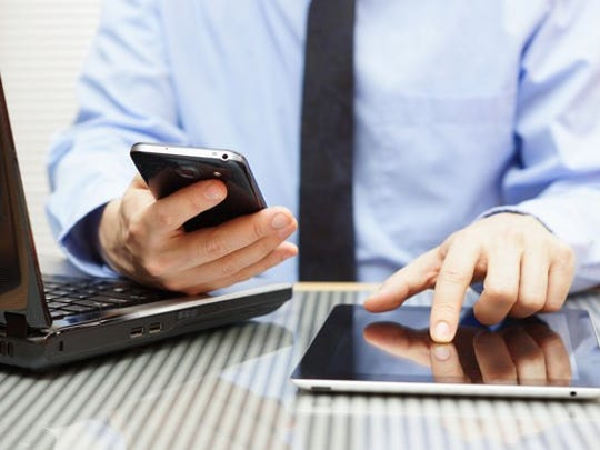 A businessman at a desk, handling a laptop, a smartphone, and a tablet.