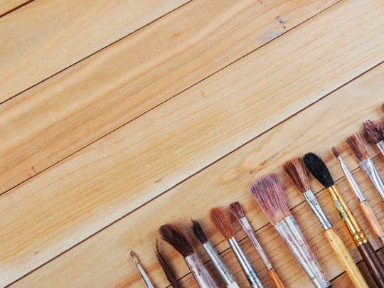 Paintbrushes and art tools on a wooden table background