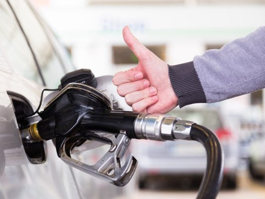 closeup-of-man-showing-thumb-up-gesture-pumping-gasoline-fuel-in-car-at-gas-station_large.jpg