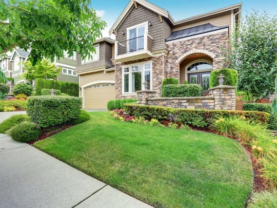 Large stone and shingle house with neatly kept, very green landscaping