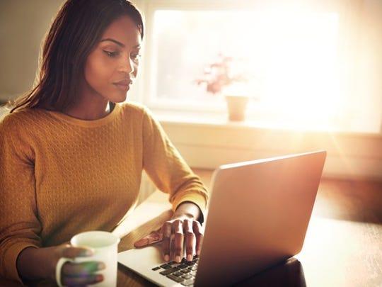 A woman types on a laptop.