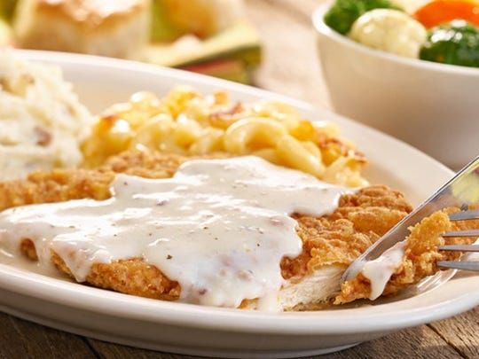 At Cracker Barrel, three sides surround fried chicken breast topped with sawmill gravy and served with a biscuit or cornbread.