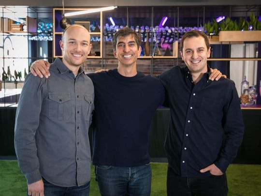 The three men are shown standing arm-in-arm at Lyft's headquarters.