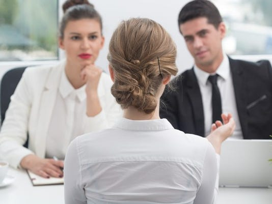 young-woman-sitting-across-desk-from-a-professionally-dressed-man-and-woman-job-interview-employee-boss-meeting_large.jpg