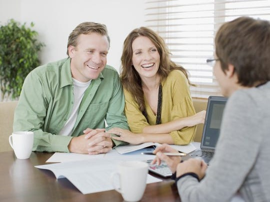 A married couple discussing their finances with an adviser.