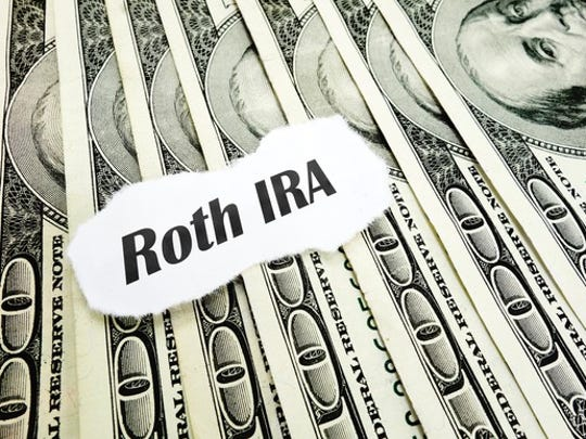 "A piece of paper that reads ""Roth IRA"" on top of a fanned out pile of cash."