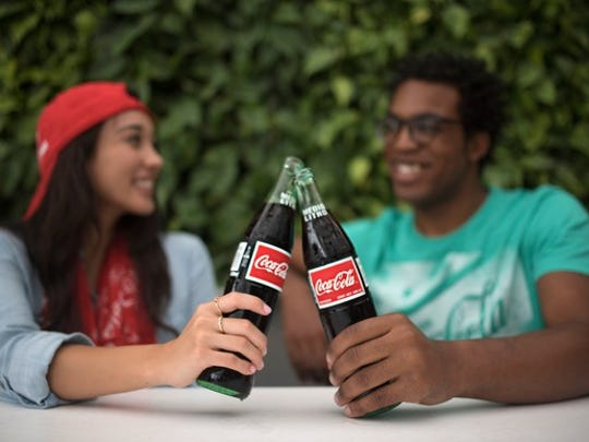 A young woman with a red hat and a young man with a green shirt are shown clinking their glass Coke bottles together