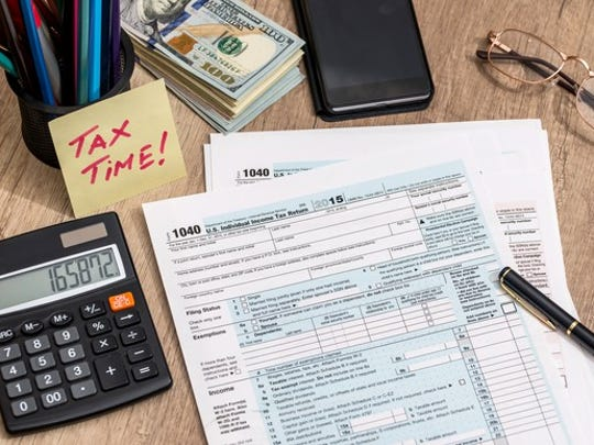A set of tax forms, a calculator, a pen, and a note which reads Tax Time, spread out on a desk