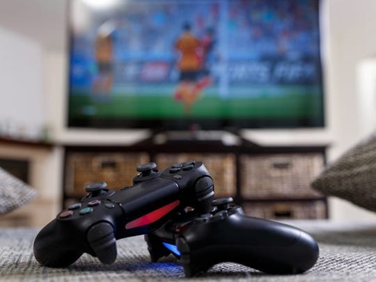 Two PlayStation 4 controllers in front of a television.