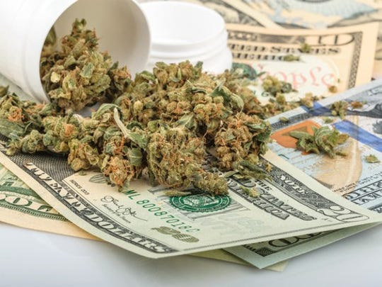 Marijuana buds spill out of a prescription bottle onto paper money spread out on a table.