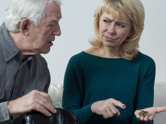 A confused elderly man staring at coins being held and pointed at by a woman next to him.