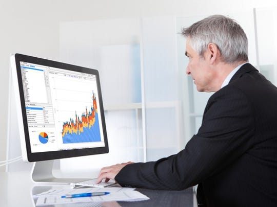 Senior man looking at computer screen with bar chart and pie chart on it