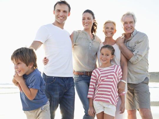 A multi-generation family portrait on a beach.