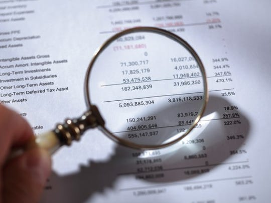 Person looking at a balance sheet with a magnifying glass.