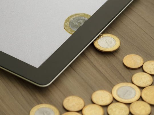 Physical coins on a table being transformed into digital coins on a tablet.