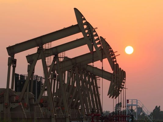 a-group-of-oil-pumps-with-the-sun-setting_large.jpg