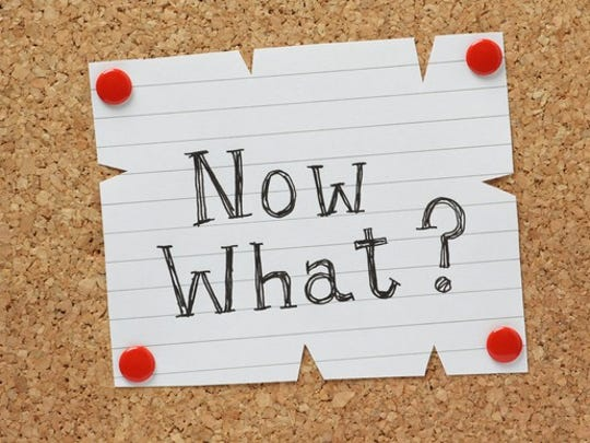 on a corkboard, a paper is tacked on, asking now what?