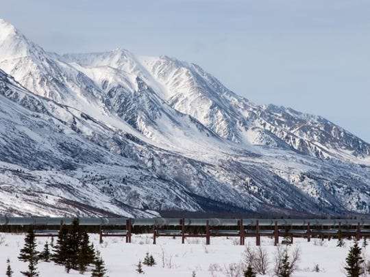 An oil pipeline near snow covered mountain.