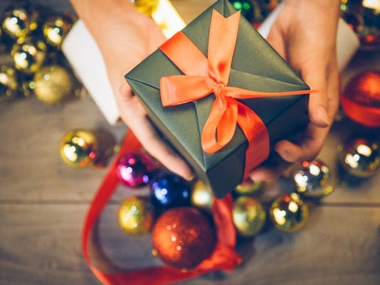 aerial-view-of-persons-hands-holding-out-a-wrapped-gift-box-over-christmas-ornaments-present-holiday_large.jpg