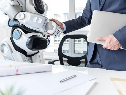 A robot and a human shake hands.