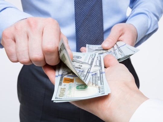 One businessman hands paper currency to another business person.