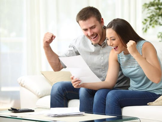 A millennial couple sitting on a couch happily as they read a piece of paper.