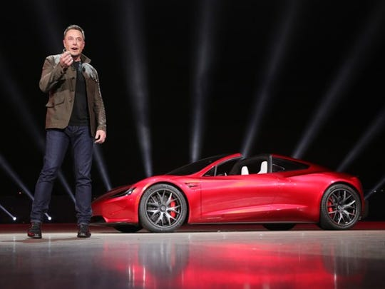 Elon Musk speaking on a stage next to a red second-generation Tesla Roadster.