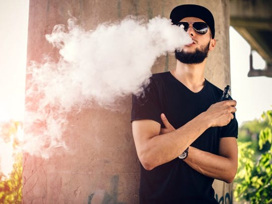 Man blowing vapor from electronic cigarette