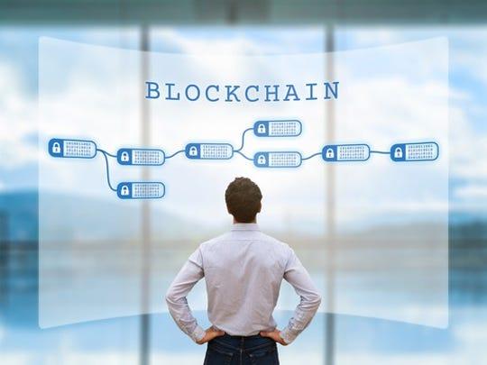 A businessman looking at a blockchain on a digital screen.