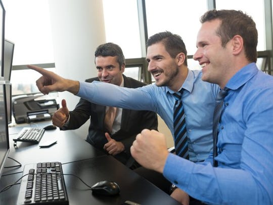 Three institutional investors cheering in front of their computers.