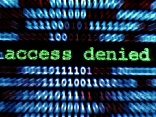 A computer screen that reads access denied, with blurred binary code in the background.
