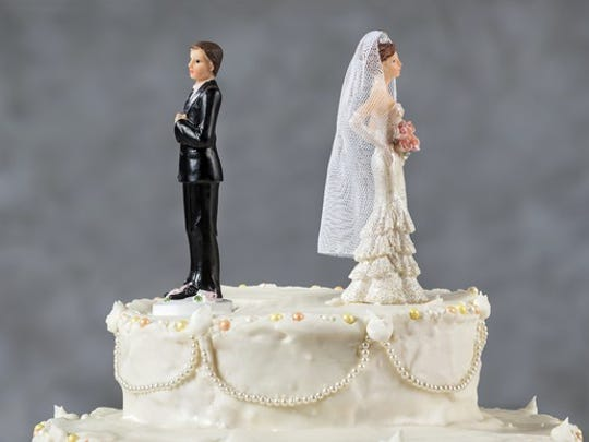Figurines on top of a wedding cake, facing away from each other.