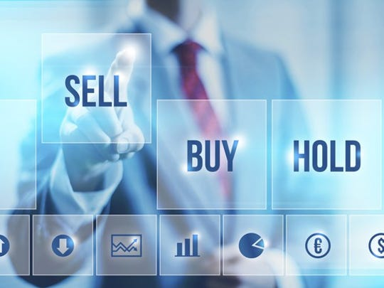 An investor pressing a digital sell key on a screen.