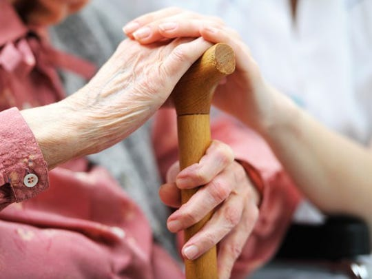 Senior citizen holding a cane and sitting with a caregiver