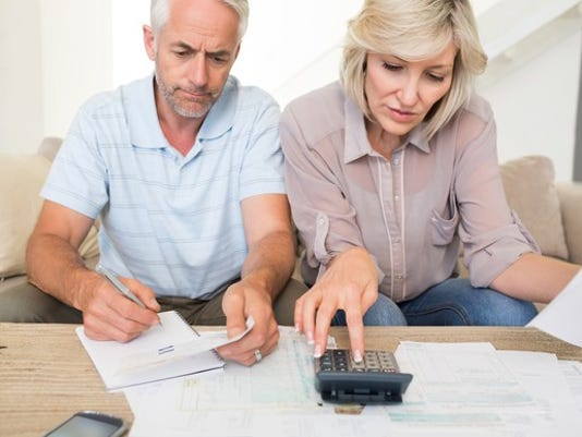 mature-couple-looking-at-documents-and-using-calculator-bills-finances_large.jpg