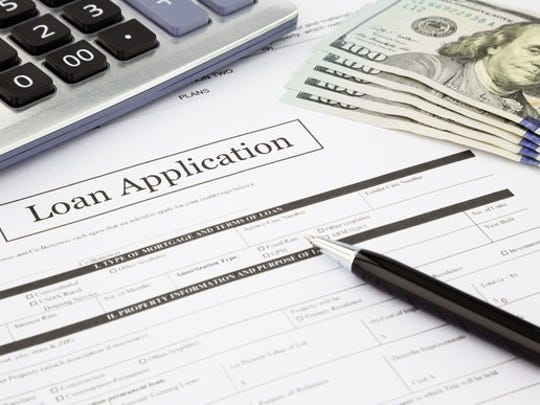 Loan application with a calculator, pen, and $100 bills on a flat surface.