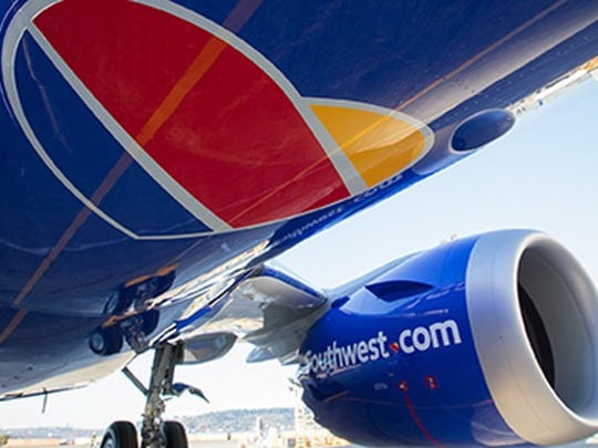 The underside of a blue Southwest Airlines Boeing 737, displaying the company name and heart shaped logo.