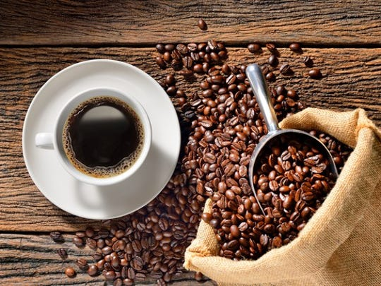 Coffee and coffee beans sitting on a wooden table.